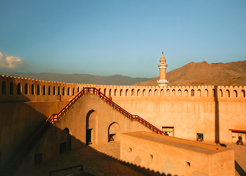The iside of Nizwa Fort in Oman glowing in the late sun, with the mosque minaret and mountains rising behind