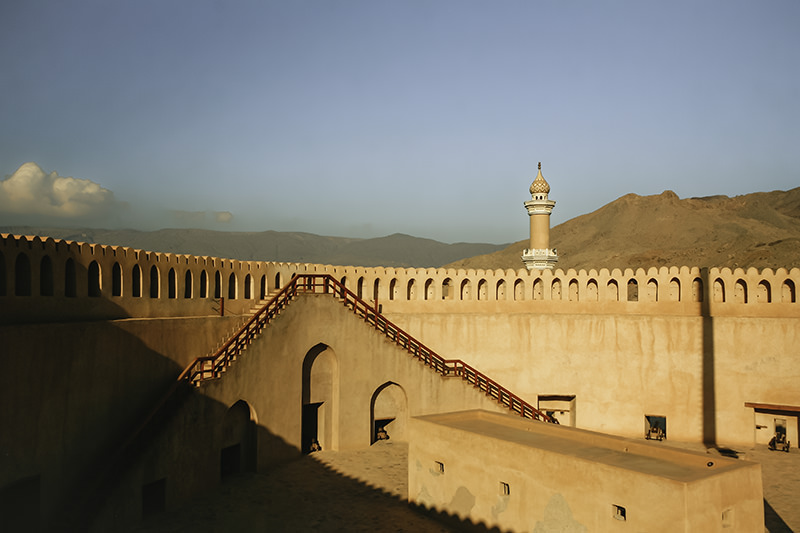 The inside of Nizwa Fort in Oman glowing in the late sun, with the mosque minaret and mountains rising behind