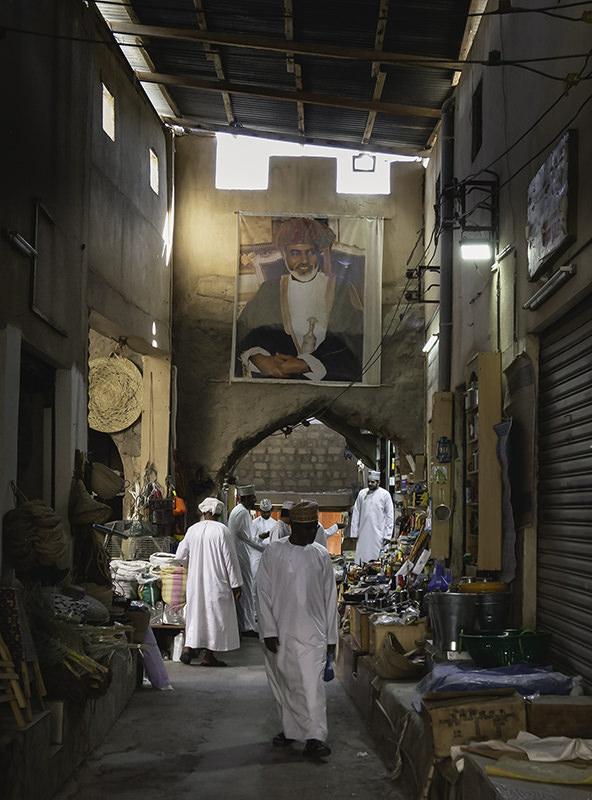 Men in traditional Omani dress shop inside the old souk in Nizwa, Oman