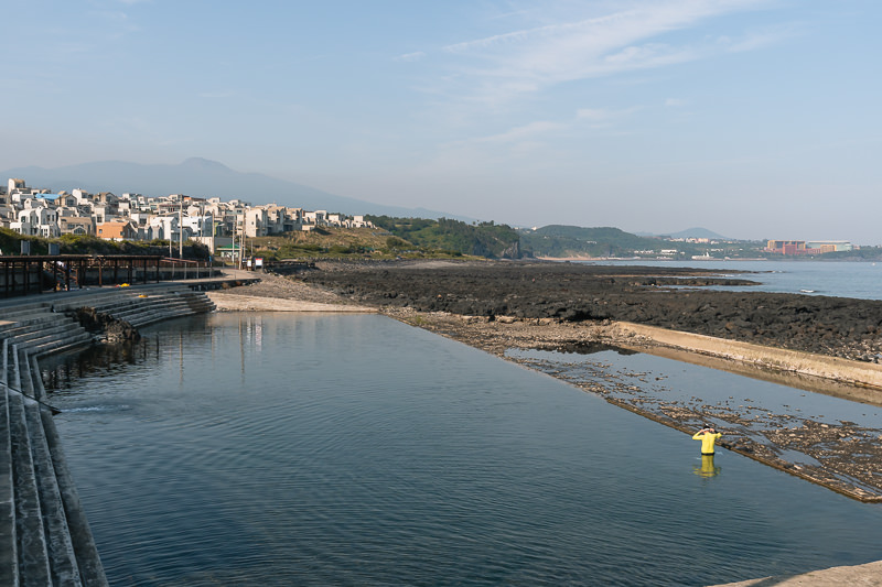 A man swims alone in Nonjinmul outdoor swimming pool on Jeju, the coast dwindling away and the faint outline of Hallasan seen against the sky