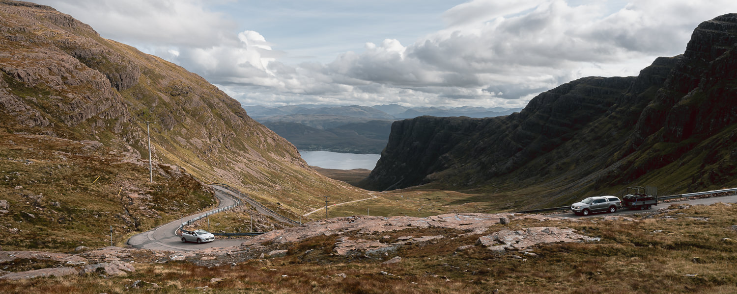 Two vehicles come face to face on the single track road near the top of the Bealach na Ba, one of the absolute best driving highlights of Scotland's North Coast 500.