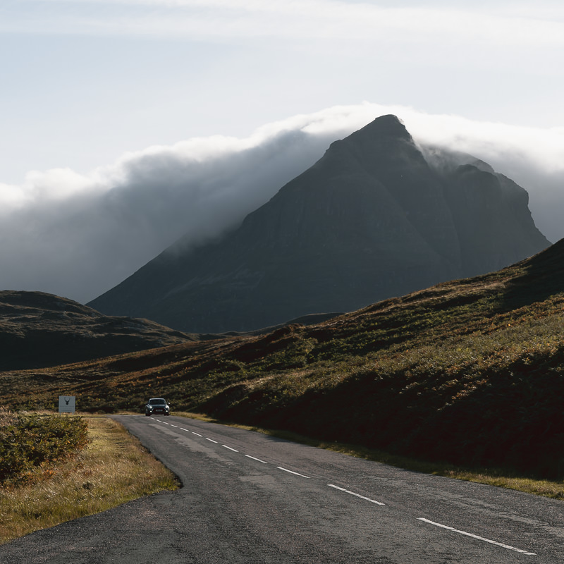 A car drives below the distinctively shaped Quinag on Scotland's North Coast 500 route.