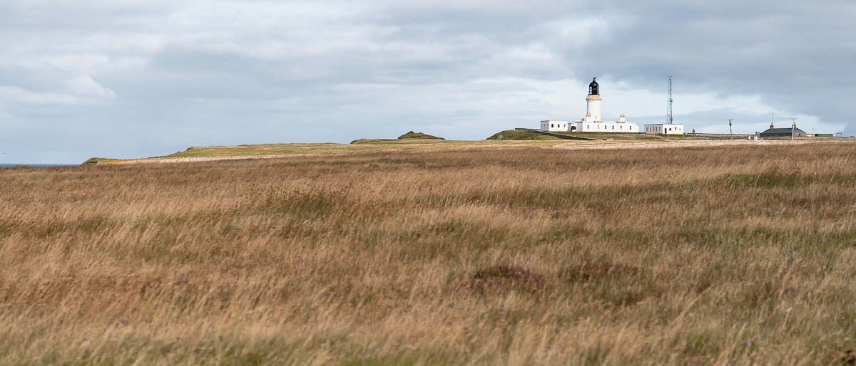 The white and yellow Stevenson lighthouse at Noss Head, just off the North Coast 500 route.