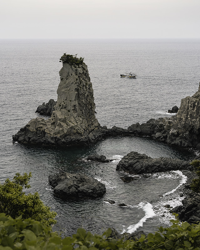 The sea stack called Oedolgae, rising 25 metrs from the sea with a tuft of foliage on top while a small fishing boat putters by behind