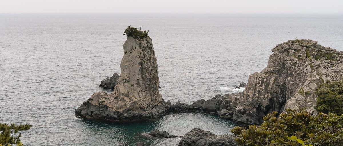 The sea stack called Oedolgae, rising 25 metrs from the sea with a tuft of foliage on top