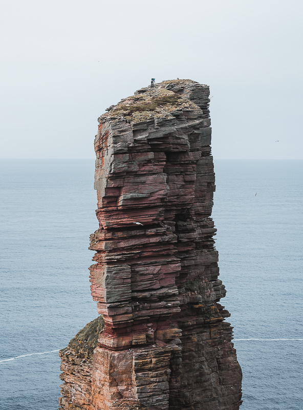 A climber pulls his friend to the top of the Old Man of Hoy, a 137 metre tall sea stack on the coast of Hoy in the Orkney Islands