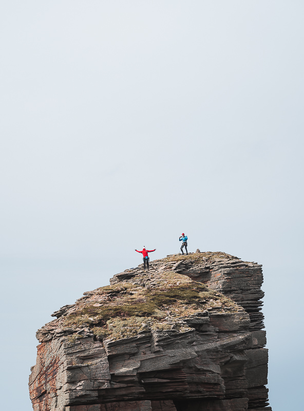 Two climbers celebrate and take pictures on top of the Old Man of Hoy