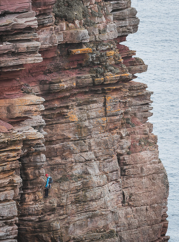 A climber descending down the side of the Old Man of Hoy