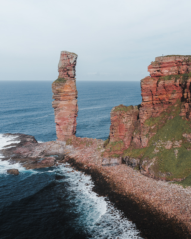An impressive view of the Old Man of Hoy from the south, showing the towering stack detatched from the rugged red cliffs of the island's west coast