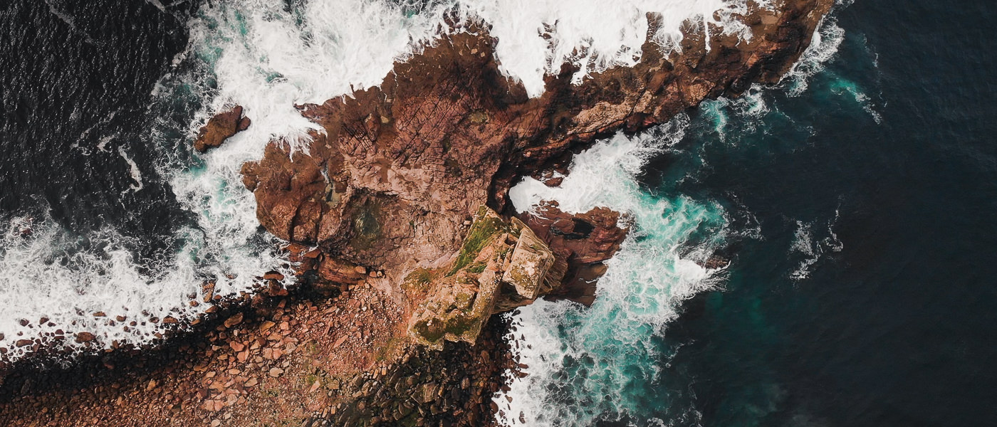A top down aerial view showing waves crash around the rocky base of the Old Man of Hoy
