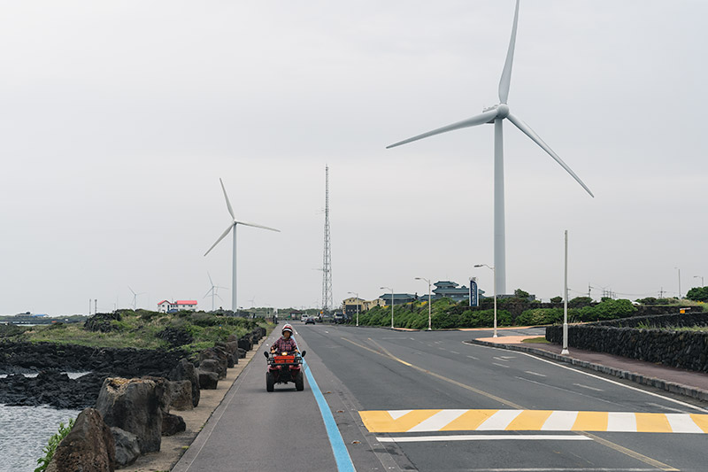 An elderly woman is driving towards the photographer in a quad bike along an empty seaside road with wind turbines behind