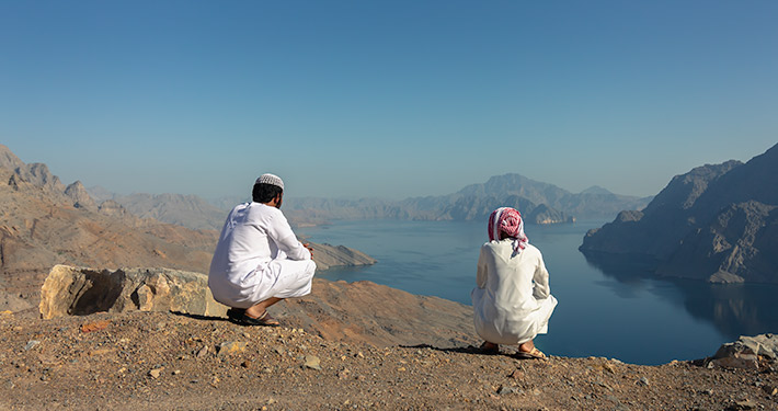 Two young men in traditional Omani dress looking over Khor Najd, Musandam, Oman