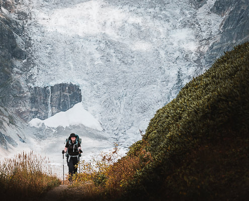 A woman hiking with backpack and poles in front of a glacier wall