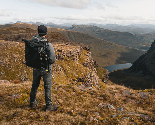 A hiker with camera bag stands looking out over the hills from the Sgurr a' Chaorachain Viewpoint above the Bealach Na Ba in Western Scotland