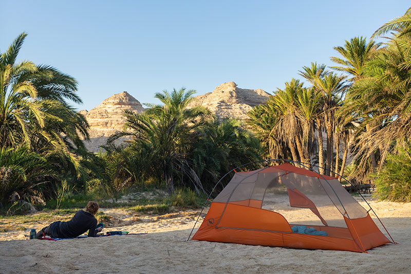 Kim relaxes on the sand next tp the tent, palm trees and sandy mountains rising behind.