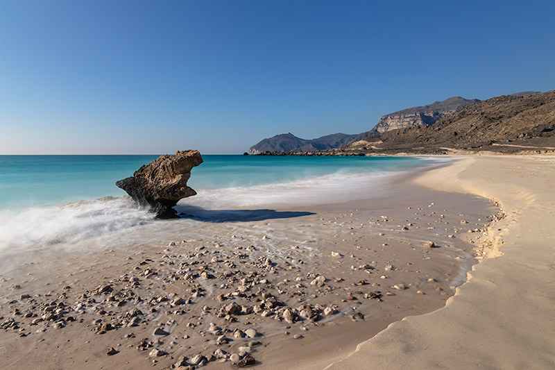 The surf crashes into the shore at Fazayah Beach, breaking over a uniquely shaped rock.