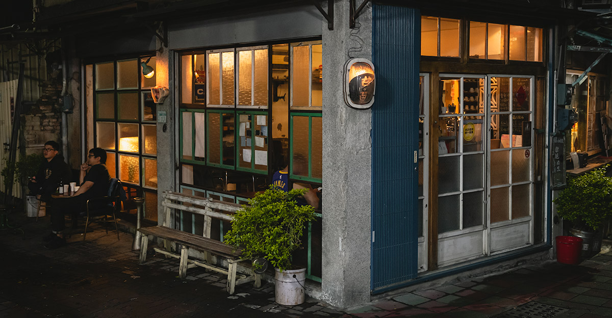 The outside of Cafe Gandan in Tainan at night. Soft yellow light comes from three big windows and two young men sit out on the bench in the warm evening