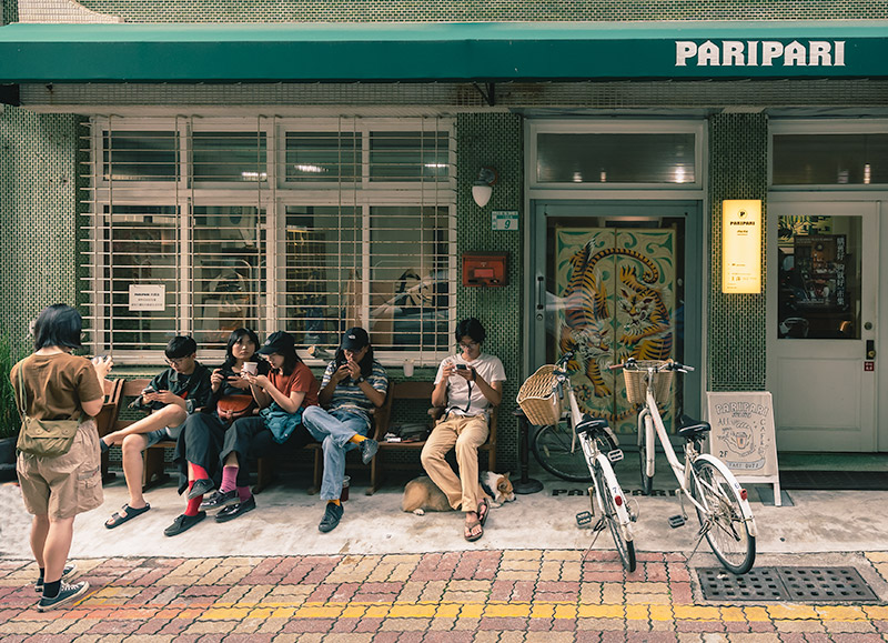 Outside the cafe and design shop PariPari in Tainan. Five young people sit on the bench, looking at their phones, next to two old style bicycles with wicker baskets. The facade is covered with distinctive small green tiles.