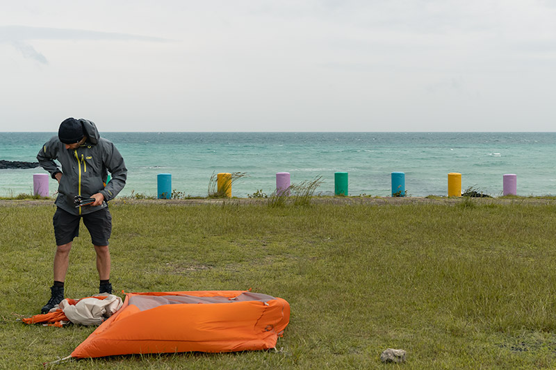 A man is packing away an orange tent with colourful bollards and blue sea behind