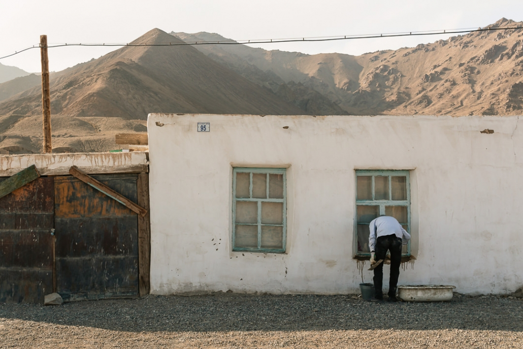 A man treats his window sills of a whitewashed house in Murghab with a dark substance. Brown mountains rise in the background.
