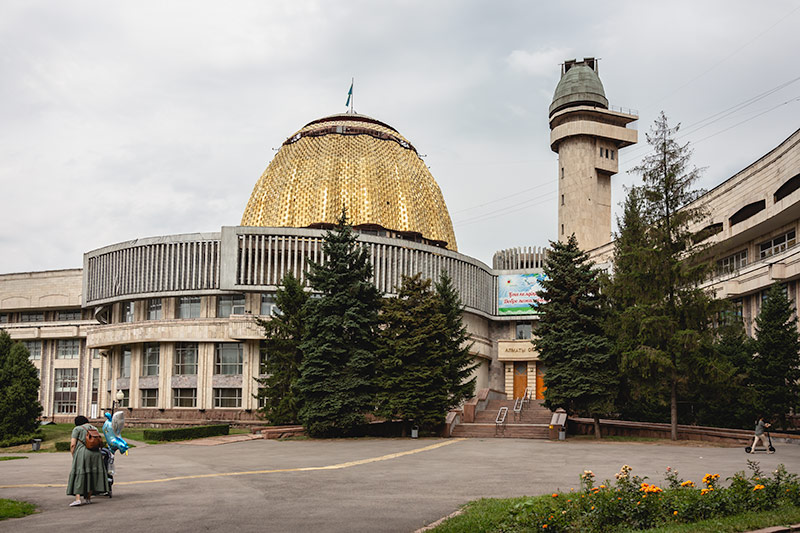 The Republican School Children's Palace (Formerly Palace of Pioneers). It's huge golden dome shines above the utilitarian concrete building on an overcast day.