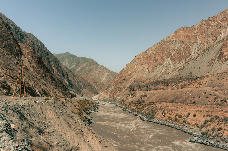 The churning fast flowing brown Panj River cuts through a steepsided gorge of dry dusty mountains, forming the border between Tajikistan on the left and Afghanistan on the right