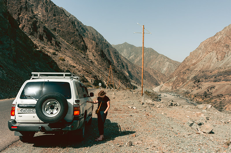 A person standing by a Toyota Lancruiser at the side of the road on a Pamir Highway road trip