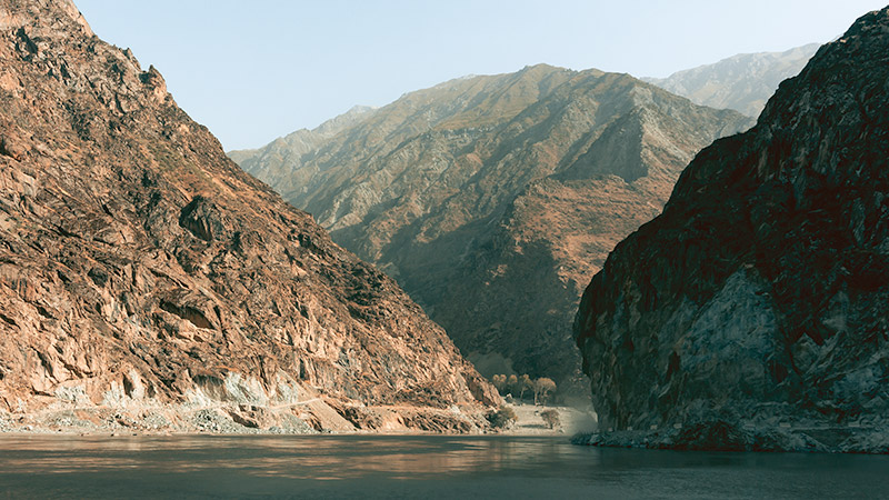 The calm and wide Panj River with the harsh mountains of Tajikistan and Afghanistan on the right and left