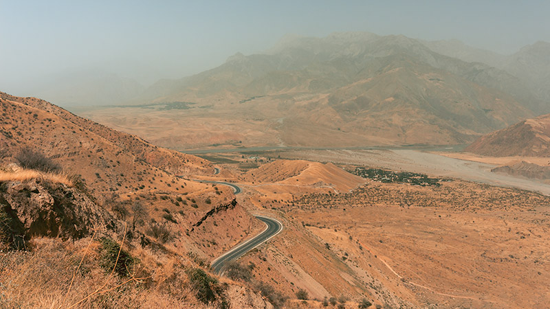 The paved road of the Pamir Highway winds down through dry land towards the Panj River