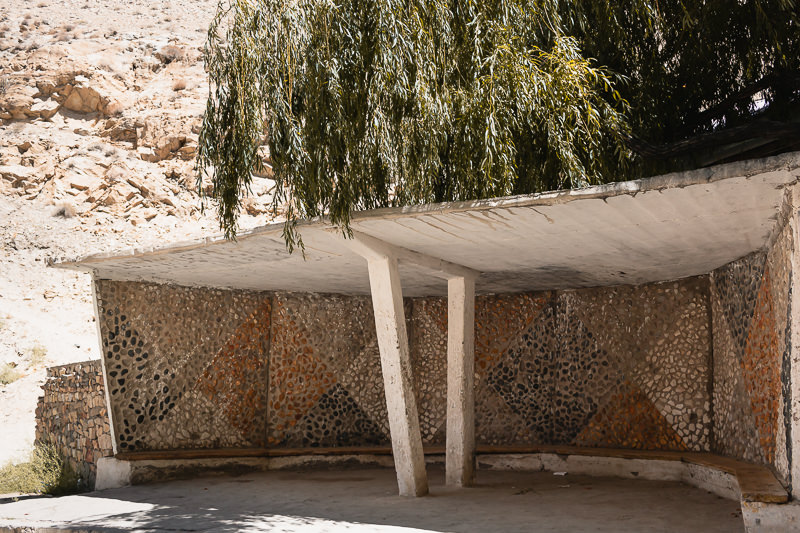 A Pamir Highway Soviet bus stop decorated with interlocking triangles of different coloured pebbles, in a village between Khorog and Ishkashim in Tajikistan