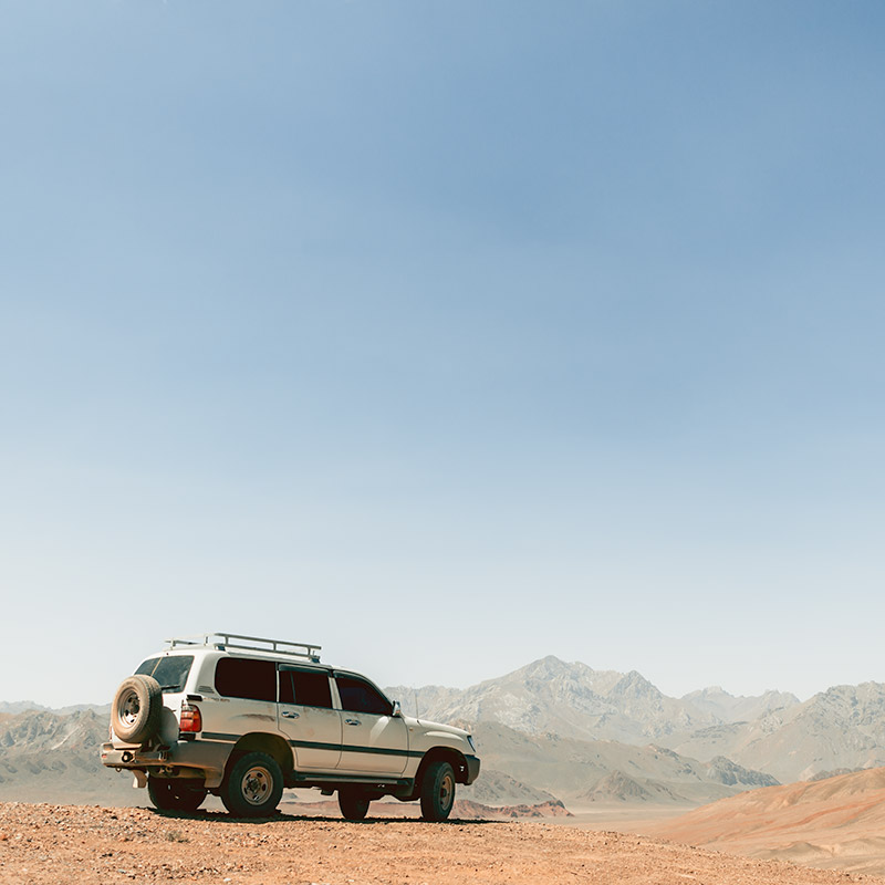 A Toyota Landcruiser parked at 4300 m with distant mountains in the background while on a Pamir Highway road trip