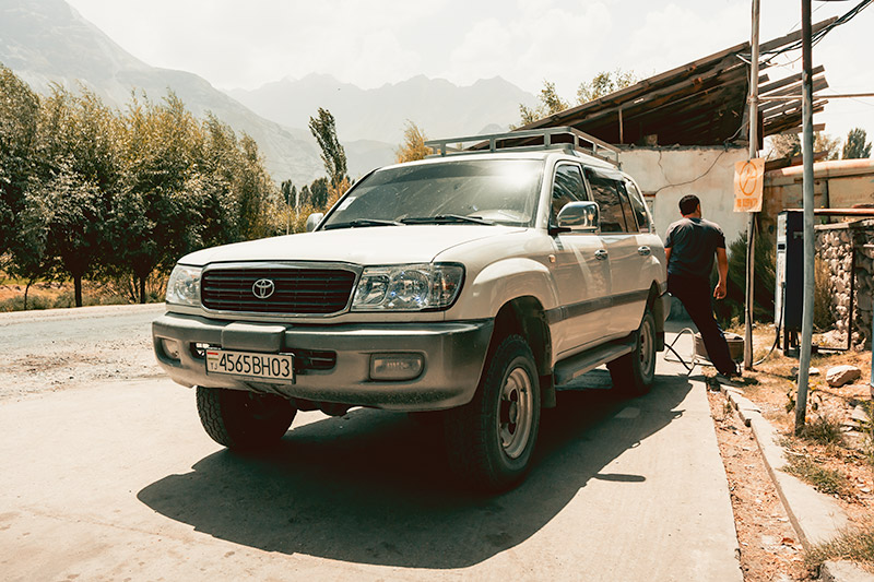 A driver filling up his Toyota Landcruiser in the sun at a petrol station on the Pamir Highway