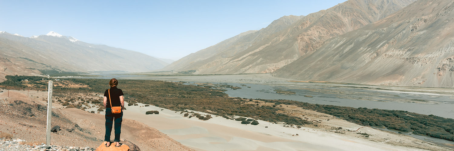A person standing on a rock looks out at the Wakhan Valley while driving the Pamir Highway in Tajikistan