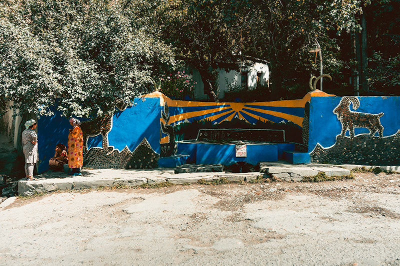 Two local women chatting next to a colourful Soviet era well in a small village on the Pamir Highway