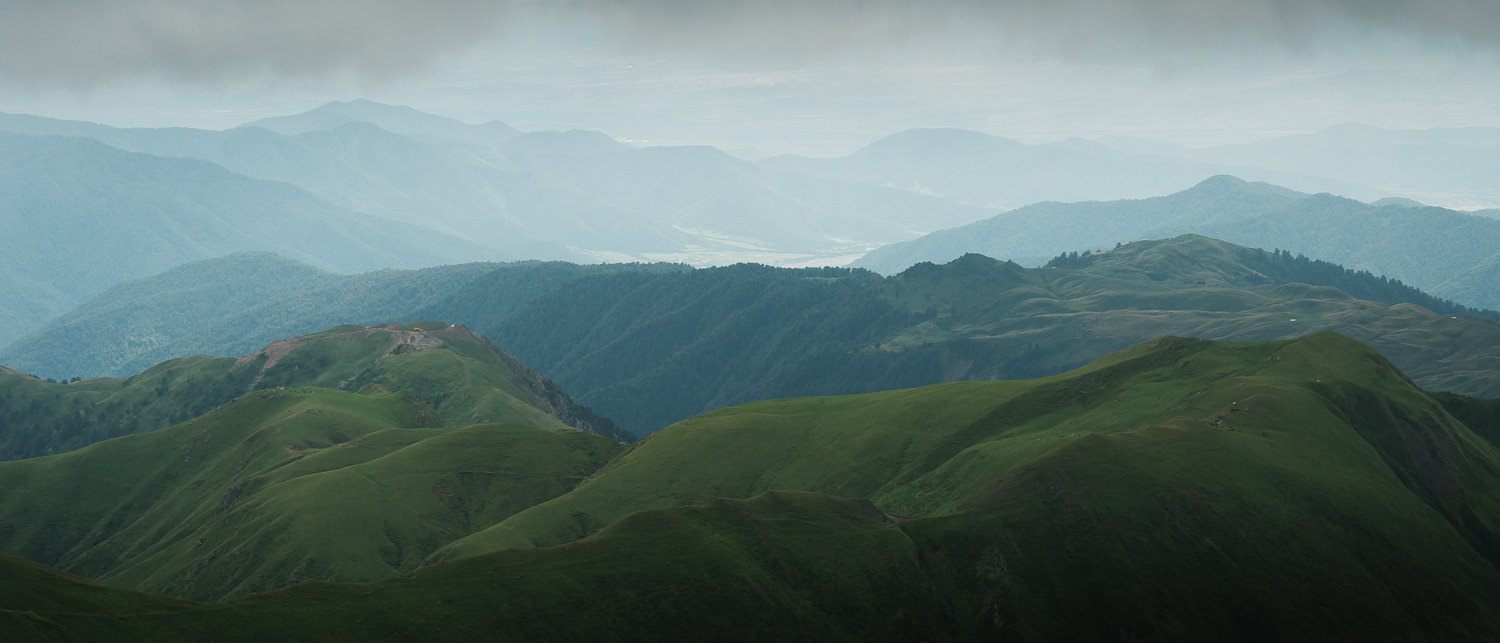 A view of sunny Pankisi valley from the gloomy overcast hills more than 2000 metres above