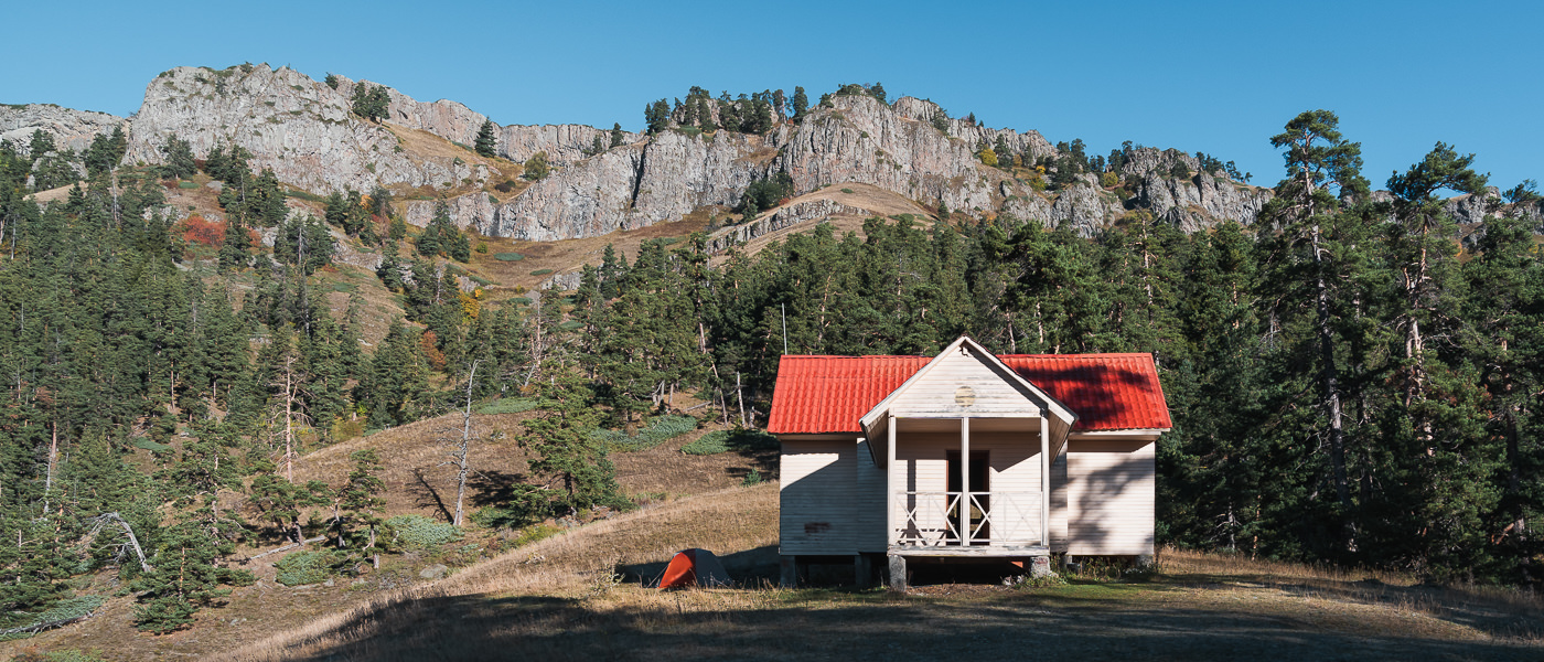 Amarati Tourist Shelter in the morning sun below towering cliffs, on the Panorama Trail in Borjomi-Kharagauli National Park