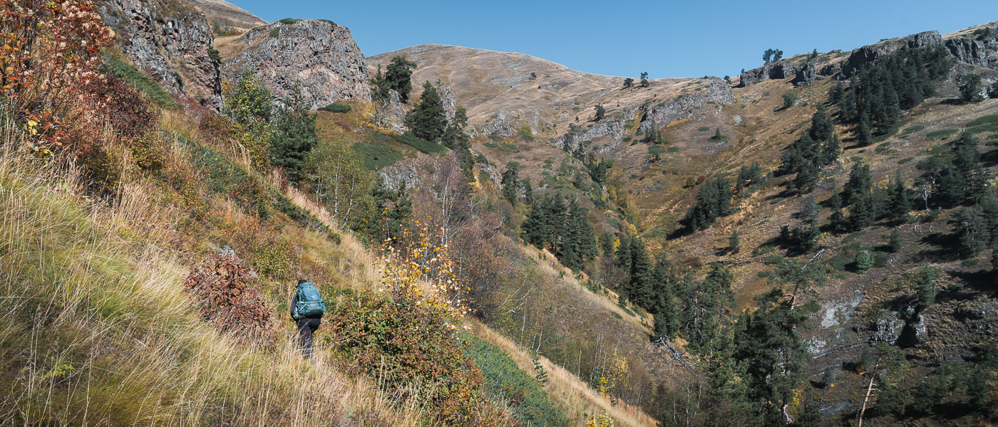 A hiker on the grassy hillside on Day 2 of the Panorama Trail in Borjomi-Kharagauli National Park