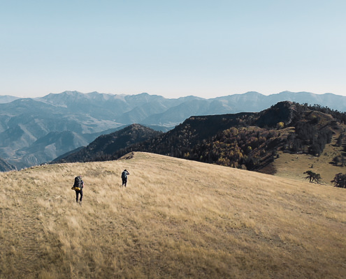 Two hikers traverse the grassy ridge on Day 2 of the Panorama Trail