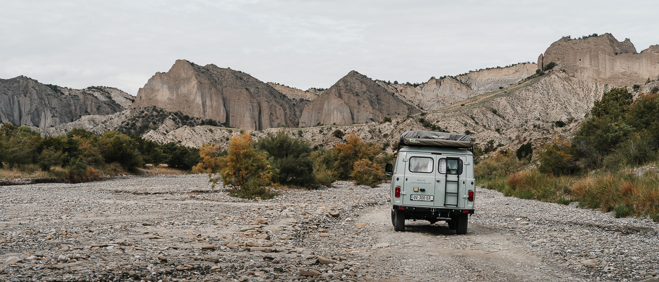 A UAZ Buhanka 4x4 camper van on the stony track in Vashlovani's Pantishara Canyon, with the ancient seabed known as Alesilebi rising in the background