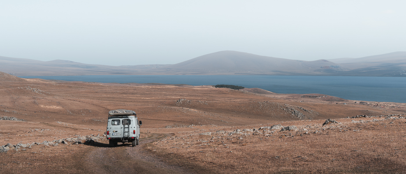 A UAZ Buhanka campervan descends a rough track towards Paravani Lake on the Javakheti Plateau in Georgia