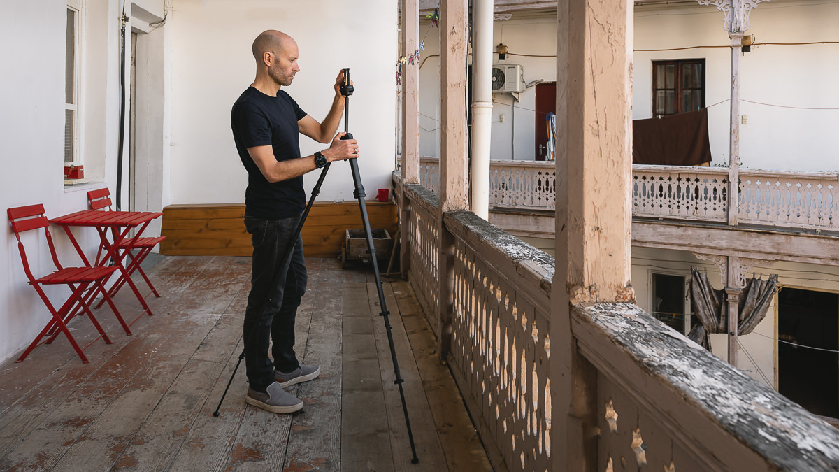A person standing on a long wooden veranda uses the phone mount on a fully extended Peak Design Travel Tripod, an essential piece of travel photography gear