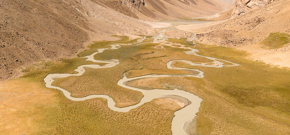 Looking down on the snakelike meandering river at green Peak Engels Meadow, a must visit place on a Pamir Highway road trip