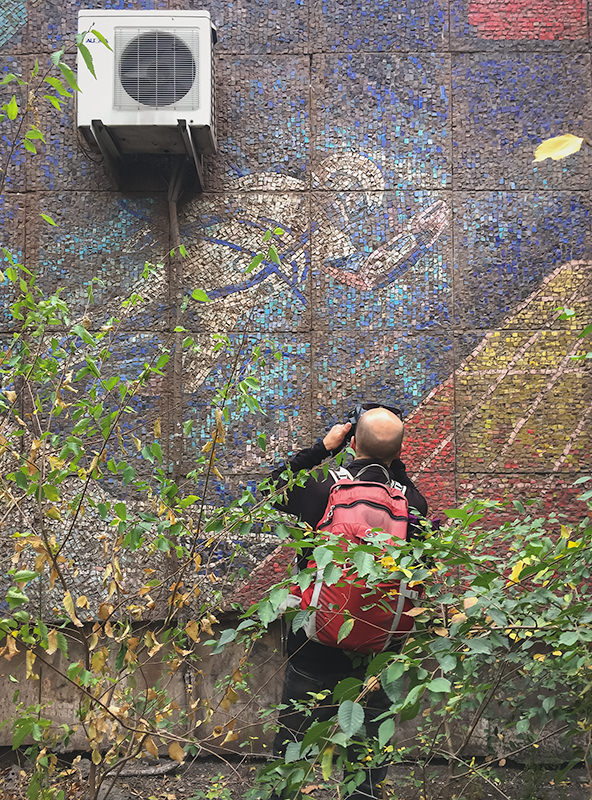 A man photographing a damaged Soviet era mosaic on a wall in Bishkek