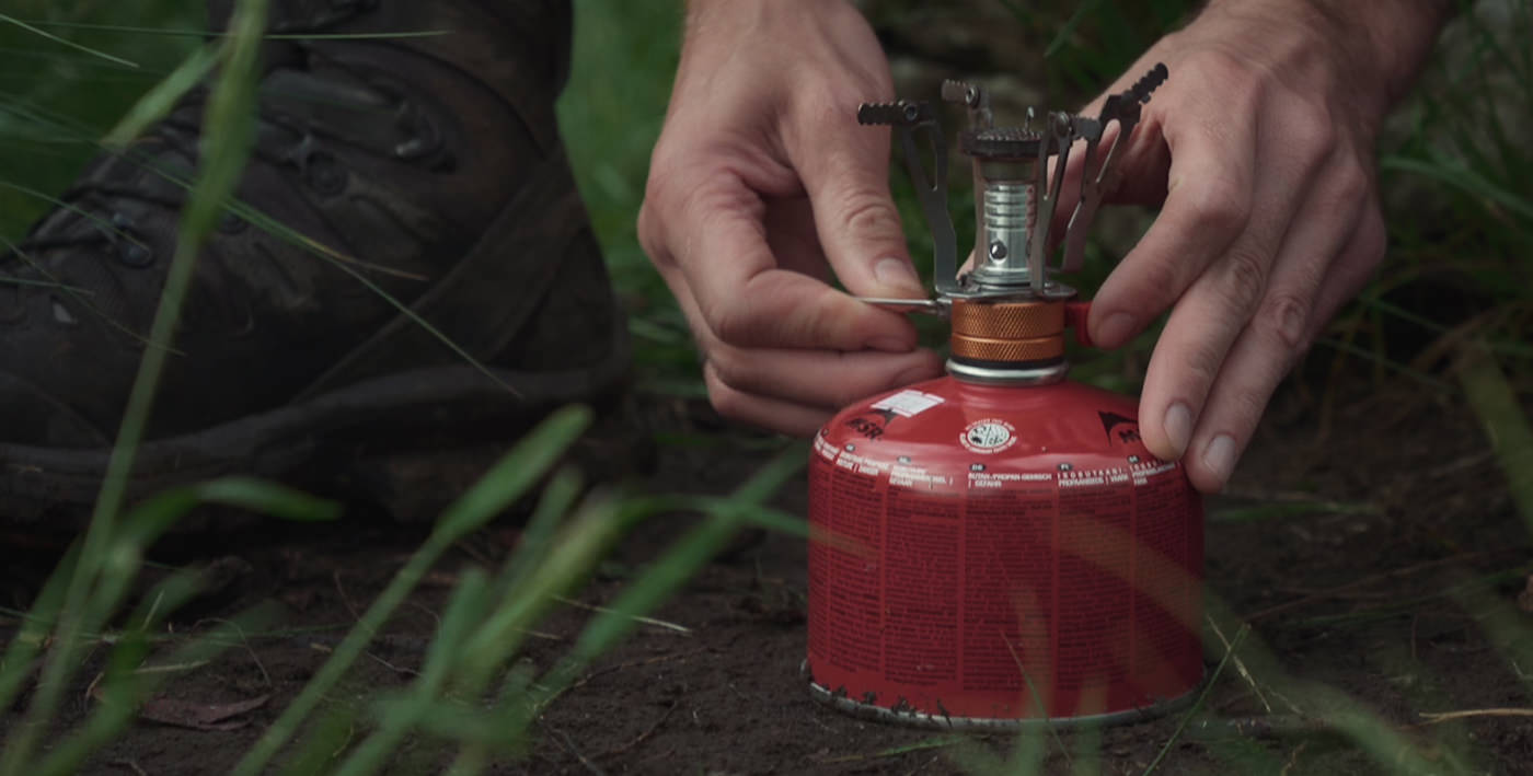 The pocket stove and gas canister, seen here being lit, is always part of our backpacking camping gear setup