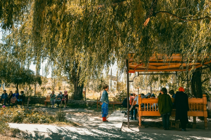 A busy outdoor place at lunchtime in a Western Pamirs village between Khorog and Ishkashim in Tajikistan. The bright sun is shaded by the thick trees and people are resting on benches and raised platforms.