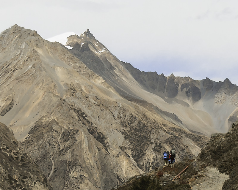 Porters dwarfed by orange and brown hued dry mountains before arriving at Yak Kharka on the Annapurna Circuit