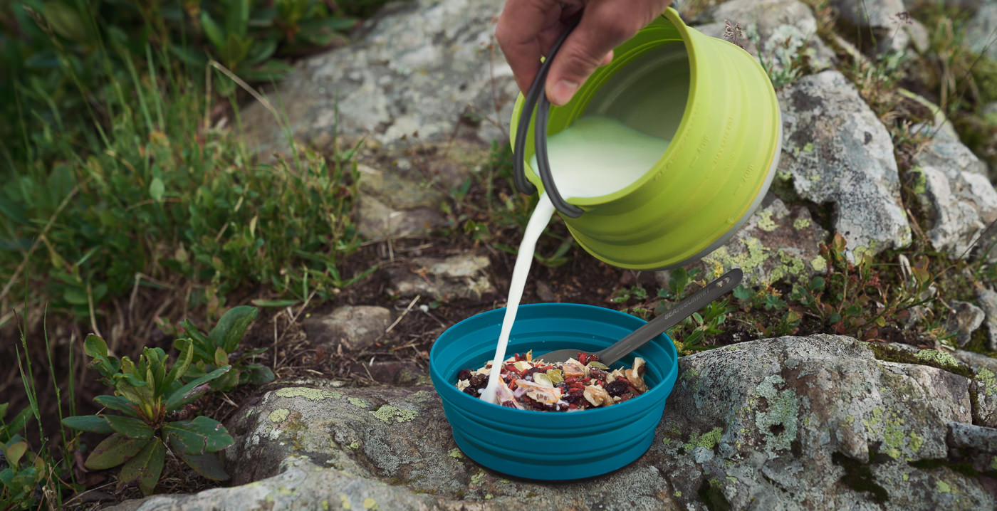 Pouring milk from the Sea to Summit X-Pot Kettle, a long serving part of our backpacking camping gear