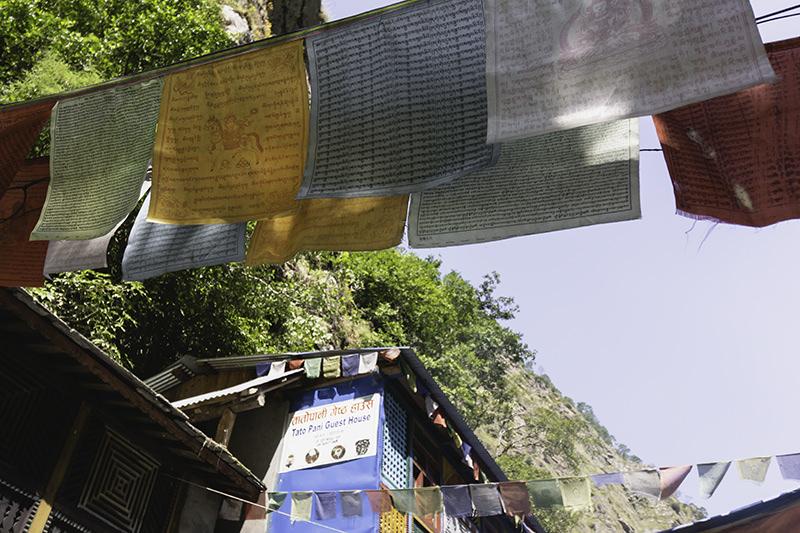 Prayer flags in the morning sun above the courtyard in Tatopani on the Manaslu Circuit Trek