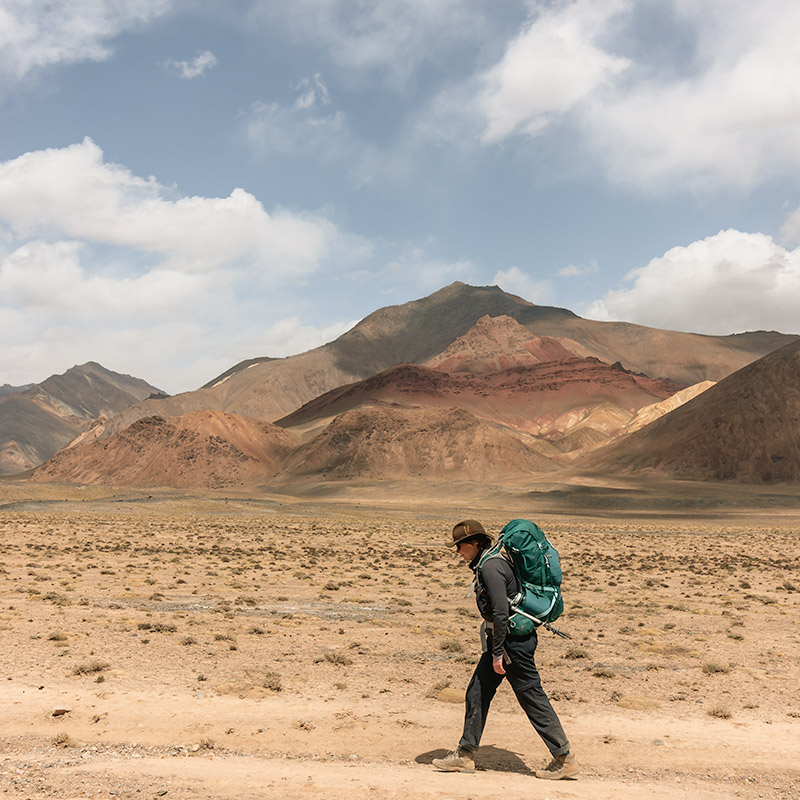 A female hiker wearing a backpack walking in the Pshart Valley with colourful mountains behind