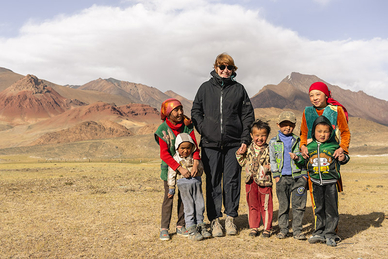 Some nomadic children and a female tourist posing for a photo in the Pshart Valley